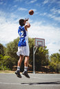 Teenage basketball player scoring while practicing in court Royalty Free Stock Photo