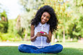 Teenage black girl using a phone african people smiling sitting on the grass Royalty Free Stock Images