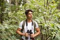 Teenage boy with binoculars hiking in forest. Summer vacation. Royalty Free Stock Photo