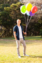 Teenage boy balloons smiling holding bunch of colorful helium Royalty Free Stock Photos