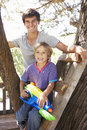 Teenage Boy And Brother Playing In Tree House Together Royalty Free Stock Photo