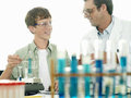 Teenage boy doing science experiment at desk in classroom teacher assisting smiling Stock Photos