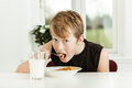 Teenage Boy Eating Breakfast Cereal in Morning Royalty Free Stock Photo