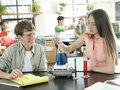 Teenage boy and girl doing science experiment at desk in classroom smiling Royalty Free Stock Image