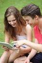 Teenage boy and girl using a tablet pc attractive relaxed happy young sitting on green grass Stock Photo