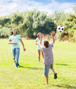 Teenage boy and happy parents playing in soccer at summer park Royalty Free Stock Images