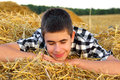 Teenage boy in the hay happy lying and dreaming Royalty Free Stock Image