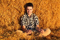 Teenage boy in the hay happy sitting Royalty Free Stock Image