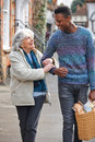 Teenage boy helping senior woman to carry shopping helps Stock Images