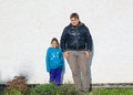 Teenage boy and little joyful happy girl standing against stucco old exterior house wall lighted by bright sunshine urban styled Royalty Free Stock Photos