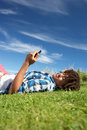 Teenage boy lying on grass with phone Royalty Free Stock Photos