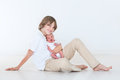 Teenage boy playing with his newborn baby brother on white background Stock Photos