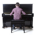 Teenage boy sits at upright piano in studio with white background Royalty Free Stock Photo