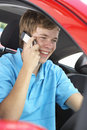 Teenage Boy Sitting In Car, Talking On Cellphone Stock Image