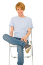 Teenage boy sitting on chair Stock Photos