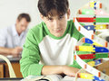 Teenage boy sitting at desk in classroom beside dna model portrait focus on foreground Royalty Free Stock Photography