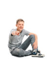 Teenage boy sitting on the floor and points at the camera happy isolated white background Stock Image