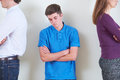 Teenage boy standing between parents who are ignoring each other stands Stock Image