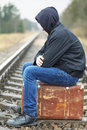 Teenage boy with a suitcase on the railway in rainy day Royalty Free Stock Photos