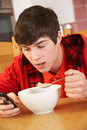 Teenage Boy Texting Whilst Eating Breakfast Stock Photos