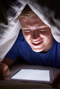 Teenage boy using digital tablet in bed at night close up of Stock Photos