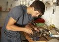 Teenage boy using workbench in garage Stock Images