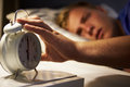 Teenage boy waking up in bed and turning off alarm clock horizontal image of Stock Image