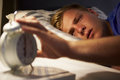 Teenage boy waking up in bed and turning off alarm clock looking sleepy Royalty Free Stock Images