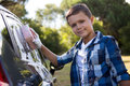 Teenage boy washing a car on a sunny day Royalty Free Stock Photo