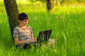 Teenage boy working on notebook in the nature having fun with sunny spring day Royalty Free Stock Photo