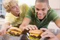 Teenage Boys Eating Burgers Stock Photo