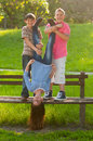 Teenage boys holding their girl friend upside down Royalty Free Stock Images