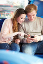 Teenage couple reading text message on bus whilst sitting down Royalty Free Stock Photos