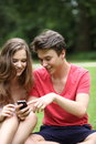 Teenage couple reading a text message on their mobile phone smiling with pleasure while sitting on grass in park Stock Image