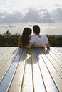 Teenage couple sitting on deck looking at view rear of loving Royalty Free Stock Images