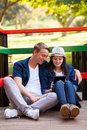 Teenage couple tablet smiling using computer sitting outdoors Royalty Free Stock Photos