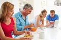 Teenage family having breakfast in kitchen with laptop chatting to each other Stock Images