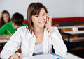 Teenage girl answering mobilephone in classroom beautiful smiling while Royalty Free Stock Photography