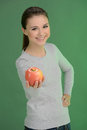 Teenage girl with apple happy teenage girl holding an apple whi while standing on coloured background Stock Photo