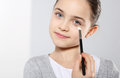 A teenage girl applying eye shadow young with brushes for make up Stock Image