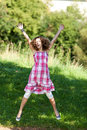 Teenage girl with arms raised jumping in nature full length portrait of park Stock Photos