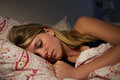 Teenage girl asleep in bed at night close up of Royalty Free Stock Images