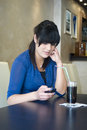 Teenage girl in bar using cell phone sitting Royalty Free Stock Image