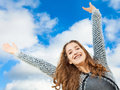 Teenage girl with beautiful long curly hair arms up in the air she looks very happy Royalty Free Stock Photography