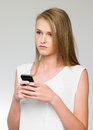 Teenage girl being bullied by text message on mobile phone looing upset Stock Photography
