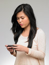 Teenage girl being bullied by text message on mobile phone looking upset Royalty Free Stock Photography