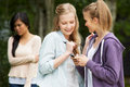 Teenage girl being bullied by text message on mobile phone upset Stock Photo
