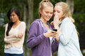 Teenage girl being bullied by text message on mobile phone upset Stock Photos