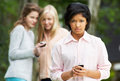 Teenage girl being bullied by text message on mobile phone upset Royalty Free Stock Photo