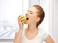 Teenage girl biting a green apple Royalty Free Stock Images
